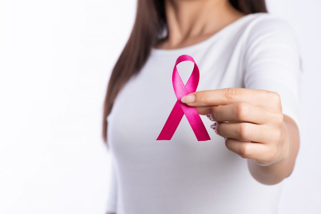 womaen hand holding pink ribbon breast cancer awareness. concept